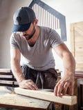 Το άτομο είναι ίσο με μια ξύλινη μηχανή άλεσης φραγμών Στοκ Εικόνα