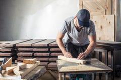 Το άτομο είναι ίσο με μια ξύλινη μηχανή άλεσης φραγμών Στοκ Εικόνες