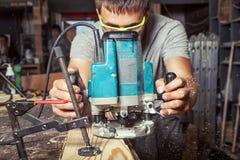 Το άτομο είναι ίσο με μια ξύλινη σανίδα με μια μηχανή άλεσης Στοκ Φωτογραφία