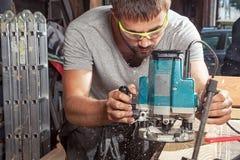 Το άτομο είναι ίσο με ξύλινο με μια μηχανή άλεσης Στοκ φωτογραφία με δικαίωμα ελεύθερης χρήσης