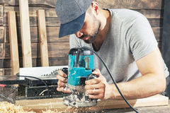 Το άτομο είναι ίσο με ξύλινο με μια μηχανή άλεσης Στοκ Εικόνες
