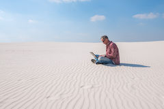 Το άτομο είναι εμπαθές για την εργασία, με ένα lap-top κάθεται στην έρημο Στοκ εικόνες με δικαίωμα ελεύθερης χρήσης