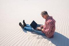 Το άτομο είναι εμπαθές για την εργασία, με ένα lap-top κάθεται στην έρημο Στοκ Εικόνα