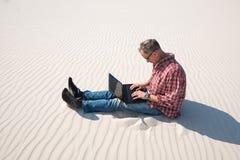Το άτομο είναι εμπαθές για την εργασία, με ένα lap-top στην έρημο Στοκ φωτογραφίες με δικαίωμα ελεύθερης χρήσης
