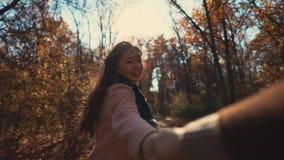 Το άτομο είναι μαγνητοσκόπηση η φίλη του που κρατά το χέρι του και που τρέχει στο ηλιόλουστο δάσος πτώσης απόθεμα βίντεο
