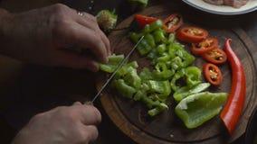 Το άτομο είναι τέμνον πράσινο πιπέρι σε έναν τέμνοντα πίνακα βίντεο φιλμ μικρού μήκους