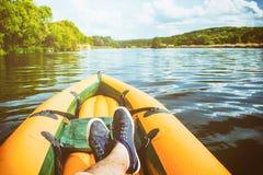 Το άτομο είναι χαλάρωση στην κίτρινη βάρκα ο ποταμός POV στοκ εικόνα με δικαίωμα ελεύθερης χρήσης