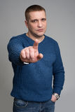 Το άτομο δείχνει το δάχτυλό του σε ένα γκρίζο υπόβαθρο Στοκ Φωτογραφίες
