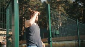 Το άτομο εισάγει το δικαστήριο, βάζει στα γυαλιά ηλίου φιλμ μικρού μήκους