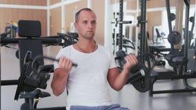 Το άτομο εκπαιδεύει τους δικέφαλους μυς στη γυμναστική φιλμ μικρού μήκους