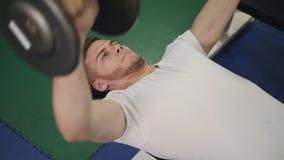 Το άτομο εκτελεί τους ανυψωτικούς αλτήρες άσκησης για τους δικέφαλους μυς στην κινηματογράφηση σε πρώτο πλάνο πάγκων, τοπ άποψη φιλμ μικρού μήκους