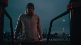 Το άτομο εκτελεί το ώθηση-UPS αθλητικό σε σύνθετο υπαίθρια στη νύχτα φιλμ μικρού μήκους