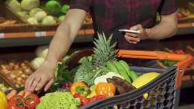Το άτομο ελέγχει τον κατάλογο αγορών του στο smartphone στοκ φωτογραφία με δικαίωμα ελεύθερης χρήσης