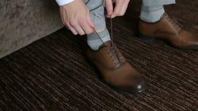Το άτομο εμπλέκει τα κορδόνια στα παπούτσια brow nleather, κινηματογράφηση σε πρώτο πλάνο φιλμ μικρού μήκους