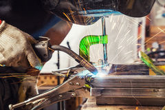 Το άτομο ενώνει στενά μια μηχανή συγκόλλησης μετάλλων Στοκ εικόνες με δικαίωμα ελεύθερης χρήσης