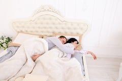 Το άτομο δεν μπορεί να κοιμηθεί το αγκάλιασμα ενώ ύπνος συζύγων Στοκ Εικόνες