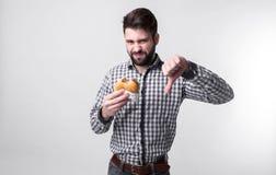Το άτομο δεν συμπαθεί το χάμπουργκερ ο σπουδαστής τρώει το γρήγορο φαγητό μη χρήσιμα τρόφιμα πολύ πεινασμένος τύπος Στοκ εικόνα με δικαίωμα ελεύθερης χρήσης