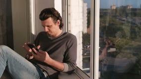 Το άτομο εξετάζει το κινητό τηλέφωνο, κτυπώντας την ταινία στα κοινωνικά δίκτυα καθμένος στο μπαλκόνι στο ηλιοβασίλεμα απόθεμα βίντεο