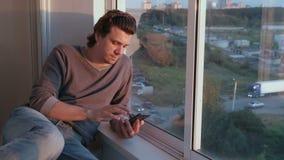 Το άτομο εξετάζει το κινητό τηλέφωνο, κτυπώντας την ταινία στα κοινωνικά δίκτυα καθμένος στο μπαλκόνι στο ηλιοβασίλεμα φιλμ μικρού μήκους