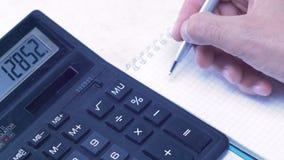 Το άτομο εξετάζει στον υπολογιστή και παραγωγή των σημειώσεων σε ένα σημειωματάριο απόθεμα βίντεο