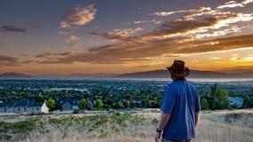 Το άτομο εξετάζει στο δέο ένα χρυσό ηλιοβασίλεμα πέρα από μια ειρηνική πόλη στοκ φωτογραφία με δικαίωμα ελεύθερης χρήσης