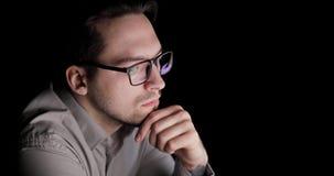 Το άτομο εξετάζει την οθόνη στη συνεδρίαση σκοταδιού και σκέψης στον εργασιακό χώρο απόθεμα βίντεο