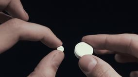 Το άτομο εξετάζει το μικρό χάπι και το μεγάλο χάπι στο στενό επάνω πυροβοληθε'ν μαύρο υπόβαθρο POV χεριών απόθεμα βίντεο