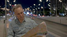 Το άτομο εξετάζει το χάρτη πόλεων και εγκαταλείπει το στηθαίο τη νύχτα απόθεμα βίντεο