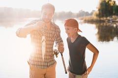 Το άτομο επίασε ένα μεγάλο ψάρι και το παρουσιάζει στο γιο του Στέκονται στο υπόβαθρο του ποταμού Στοκ Εικόνες