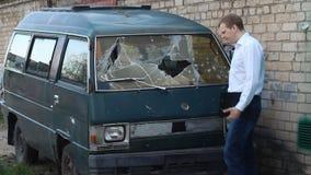 Το άτομο επιθεωρεί ένα σπασμένο μικρό λεωφορείο αυτοκινήτων, ασφάλεια απόθεμα βίντεο