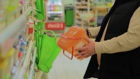 Το άτομο επιλέγει ένα εμπορευματοκιβώτιο για τα τρόφιμα στο κατάστημα απόθεμα βίντεο