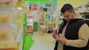 Το άτομο επιλέγει ένα εμπορευματοκιβώτιο για τα τρόφιμα στο κατάστημα φιλμ μικρού μήκους