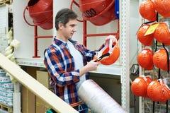 Το άτομο επιλέγει και αγοράζει το κράνος κατασκευής στο κατάστημα Στοκ Εικόνες