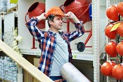 Το άτομο επιλέγει και αγοράζει το κράνος κατασκευής στο κατάστημα Στοκ φωτογραφίες με δικαίωμα ελεύθερης χρήσης