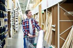 Το άτομο επιλέγει και αγοράζει τον ξύλινο πίνακα στο κατάστημα Στοκ εικόνα με δικαίωμα ελεύθερης χρήσης