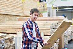 Το άτομο επιλέγει και αγοράζει τους ξύλινους πίνακες στο κατάστημα στοκ φωτογραφία με δικαίωμα ελεύθερης χρήσης