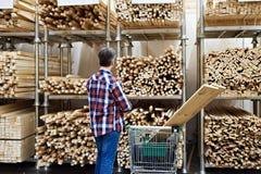 Το άτομο επιλέγει και αγοράζει τους ξύλινους πίνακες στο κατάστημα στοκ φωτογραφίες με δικαίωμα ελεύθερης χρήσης