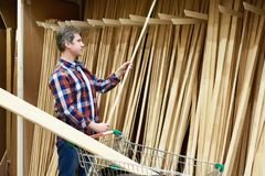 Το άτομο επιλέγει και αγοράζει τους ξύλινους πίνακες στο κατάστημα στοκ εικόνες με δικαίωμα ελεύθερης χρήσης