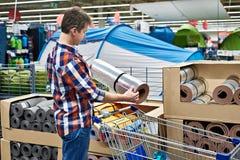 Το άτομο επιλέγει μια κουβέρτα τουριστών στο αθλητικό κατάστημα Στοκ Εικόνες