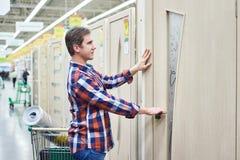 Το άτομο επιλέγει την ξύλινη πόρτα στην οικοδόμηση του καταστήματος Στοκ φωτογραφίες με δικαίωμα ελεύθερης χρήσης