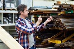 Το άτομο επιλέγει τη γωνία και rebar το δομικό χάλυβα στο κατάστημα Στοκ Εικόνες
