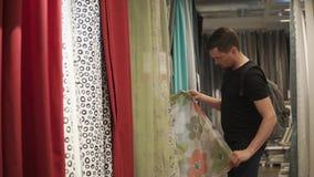 Το άτομο επιλέγει τις κουρτίνες, αισθάνεται το ύφασμα και εξετάζει τα χρώματα σε ένα κατάστημα απόθεμα βίντεο