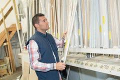 Το άτομο επιλέγει τους πίνακες για το κατάστημα κατασκευής στοκ εικόνα
