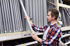 Το άτομο επιλέγει τους πλαστικούς σωλήνες υπονόμων στην οικοδόμηση του καταστήματος Στοκ εικόνα με δικαίωμα ελεύθερης χρήσης