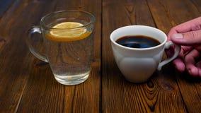 Το άτομο επιλέγει το φλιτζάνι του καφέ αντί ενός νερού με το λεμόνι για τον επιβλαβή τρόπο ζωής απόθεμα βίντεο