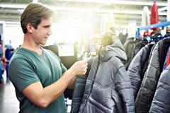 Το άτομο επιλέγει το χειμερινό σακάκι στο κατάστημα στοκ εικόνα με δικαίωμα ελεύθερης χρήσης