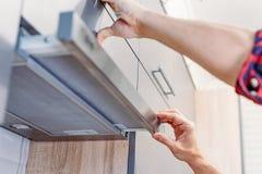 Το άτομο επισκευάζει την κουκούλα στην κουζίνα Φίλτρο αντικατάστασης στην κουκούλα κουζινών στοκ φωτογραφίες