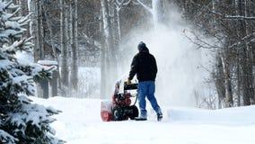Το άτομο εργάζεται με έναν ανεμιστήρα χιονιού για να αφαιρέσει το πρόσφατα πεσμένο χιόνι από driveway στοκ εικόνα