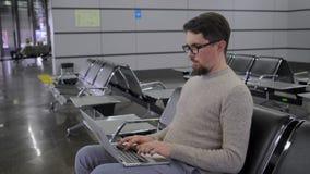 Το άτομο εργάζεται με το σημειωματάριο στο σαλόνι αναχώρησης απόθεμα βίντεο