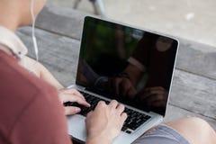 Το άτομο εργάζεται με τη χρησιμοποίηση ενός φορητού προσωπικού υπολογιστή στο εκλεκτής ποιότητας ξύλινο tabl στοκ φωτογραφίες με δικαίωμα ελεύθερης χρήσης